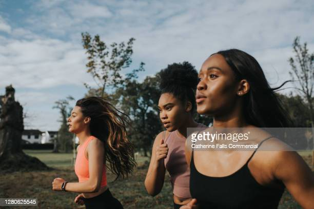 determined woman joggers - competition group stock pictures, royalty-free photos & images