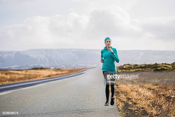 Determined woman jogging on country road