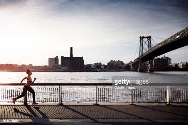 Determined woman jogging on promenade with Williamsburg Bridge in background