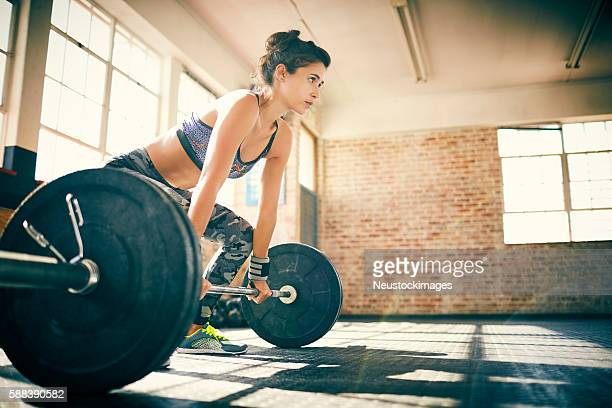 Determined woman lifting barbell in gym