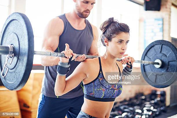 Determined woman lifting barbell while coach assisting her