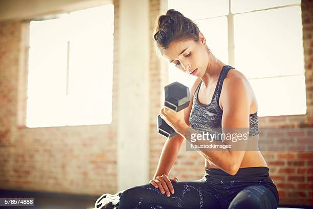 Determined woman looking at biceps while lifting dumbbell in gym