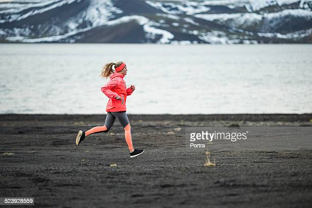 Determined woman running at lakeside during winter