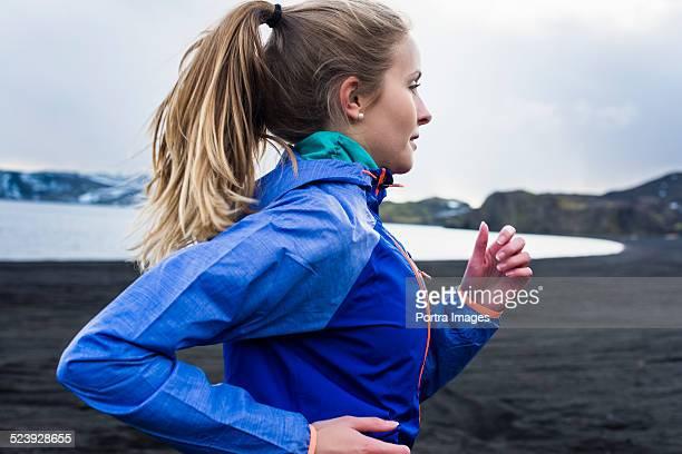 determined woman running at lakeside - abbigliamento sportivo foto e immagini stock