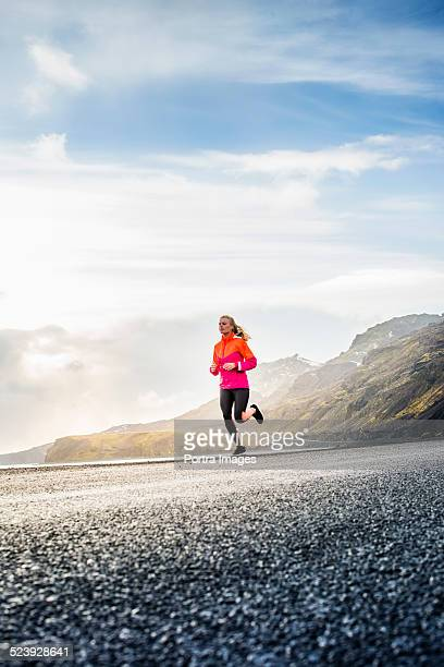 determined woman running on mountain road - joggeuse photos et images de collection