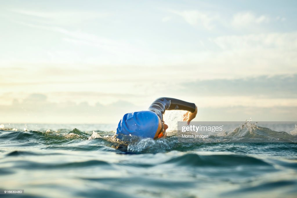 Determined woman swimming in sea : Stock Photo