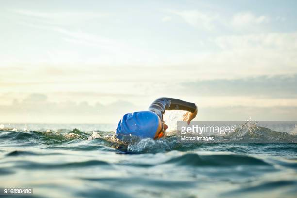 determined woman swimming in sea - competizione foto e immagini stock