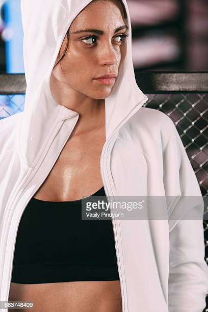 Determined woman wearing white hooded shirt standing against fence