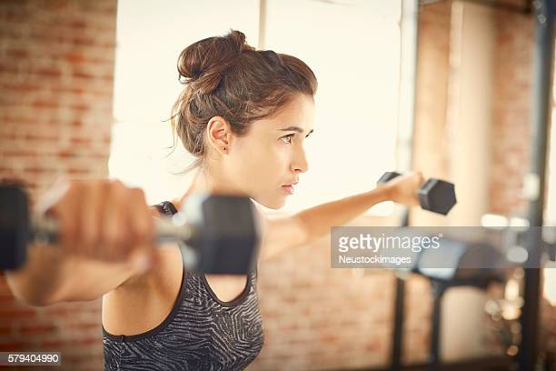 Determined woman with arms outstretched lifting dumbbells