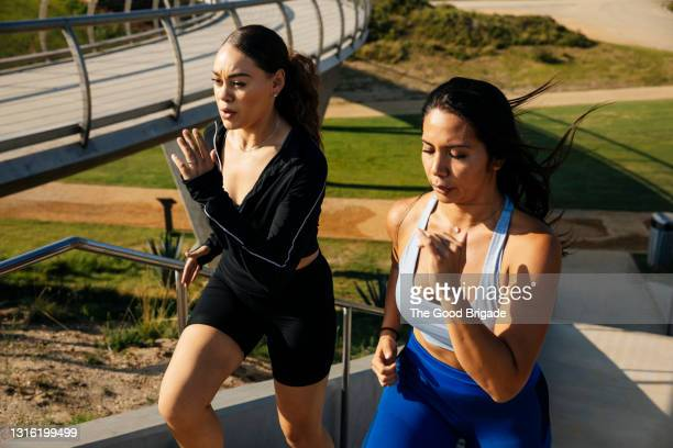 determined women exercising at park - moving up stock pictures, royalty-free photos & images