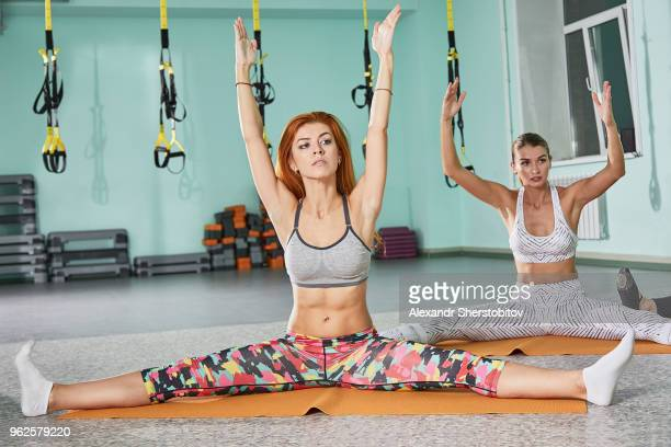 Determined women practicing yoga on mats at health club