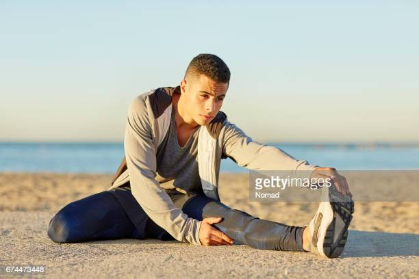 Determined young male stretching leg at beach