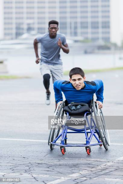Determined young man in wheelchair racing, with friend