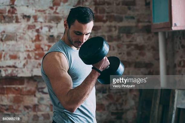 Determined young man lifting dumbbell at gym