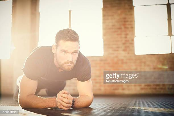 Determined young man performing plank position in gym