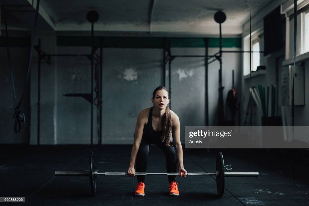 Determined young woman doing deadlift in the gym : Stock Photo