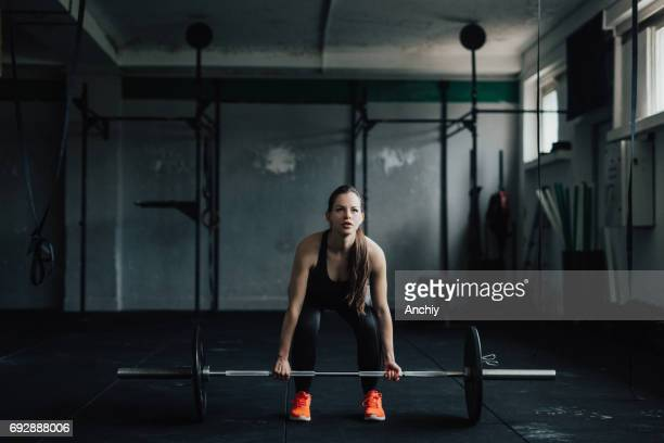 determined young woman doing deadlift in the gym - snatch weightlifting stock photos and pictures