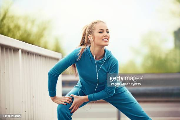 determined young woman doing warm up exercises by railing - 足を開く ストックフォトと画像