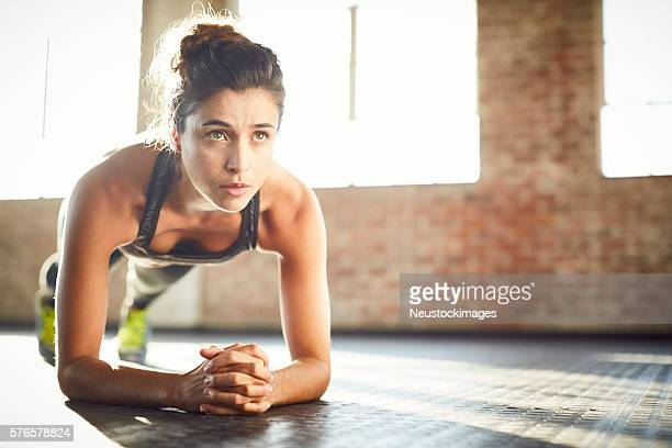 Determined young woman performing plank position in gym