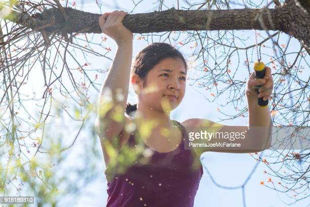 DIY, entschlossene junge Frau Rebschnitt Ast mit Handsäge