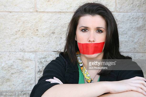determined young woman sits with red tape over her mouth - protestor stock pictures, royalty-free photos & images