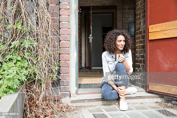 Determined young woman sitting on doorstep