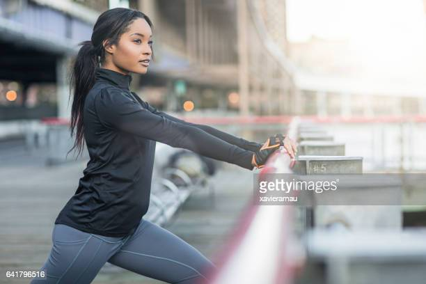 Determined young woman warming up by railing