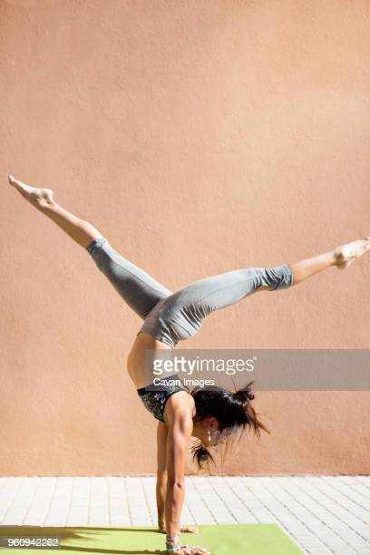 Determined young woman with legs apart doing handstand on sidewalk