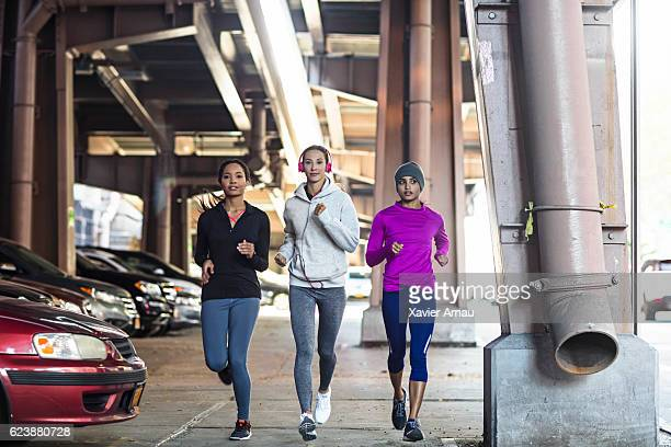 Determined young women jogging under bridge
