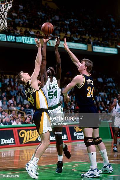 Detlef Schrempf and Rik Smits of the Indiana Pacers jumps for a rebound against Ed Pinckney of the Boston Celtics during a game played in 1992 at the...