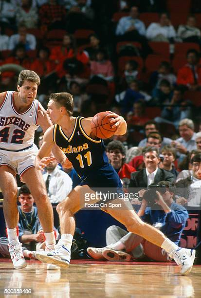 Detlef Schrempf of the Indiana Pacers drives on Mike Gminski of the Philadelphia 76ers during an NBA basketball game circa 1990 at The Spectrum in...