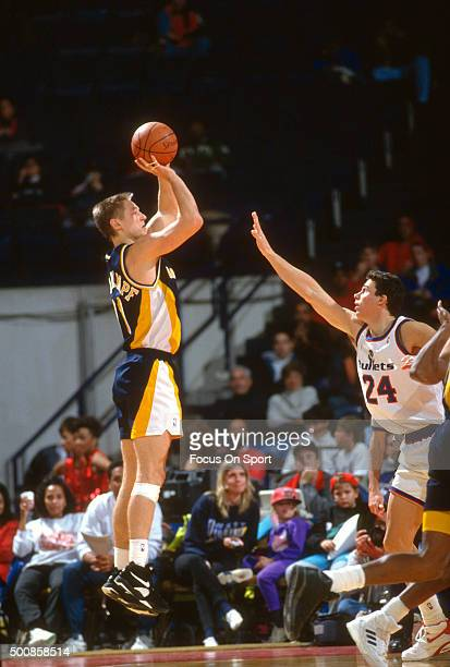 Detlef Schrempf of the Indiana Pacers shoots over Tom Gugliotta of the Washington Bullets during an NBA basketball game circa 1992 at the Capital...