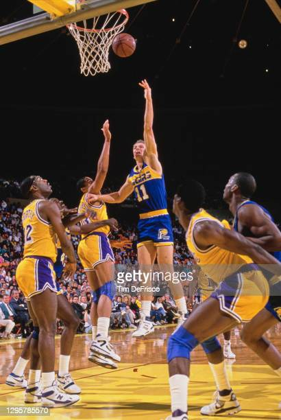 Detlef Schrempf, Power Forward for the Indiana Pacers makes a jump shot to the basket as Mychal Thompson of the Los Angeles attempts to block during...
