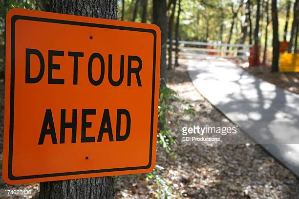 detour ahead sign on a tree in the woods - detour sign stock photos and pictures