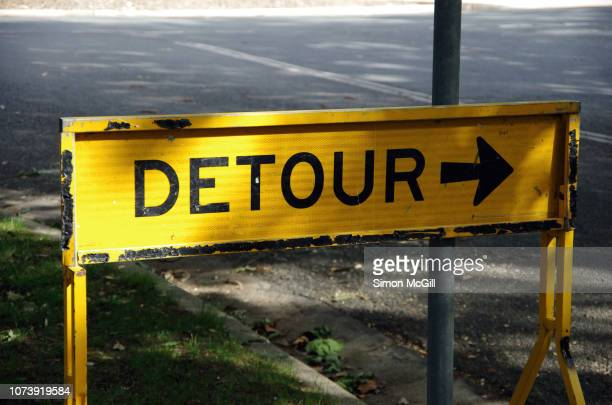 detour road warning sign on the grass shoulder of a suburban street - detour sign stock photos and pictures
