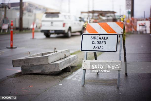 detour sign on city sidewalk outside a construction site - barricade stock pictures, royalty-free photos & images