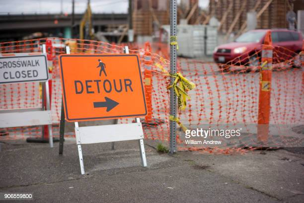 detour sign on city sidewalk outside a construction site - road construction stock photos and pictures
