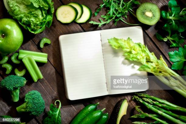 Detox diet concept: blank recipe book with detox vegetables