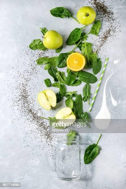 Detox drink concept Ingredients for smoothie green spinach leaves apple orange yogurt splash mason jar cocktail tube over gray texture background...