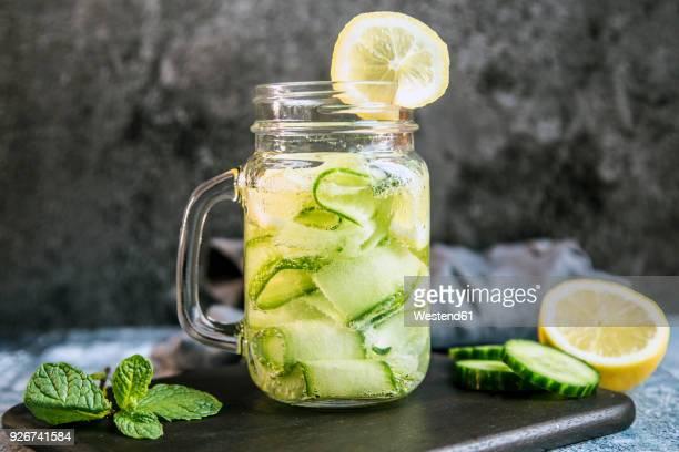 detox water, cucumber water, lemon, mint in a glass - gurke stock-fotos und bilder