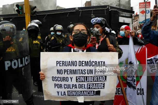 """Detractor of the new Peruvian President Pedro Castillo holds a signal that reads """"Peruvian democrat: do not allow a dark and freedomless Peru because..."""