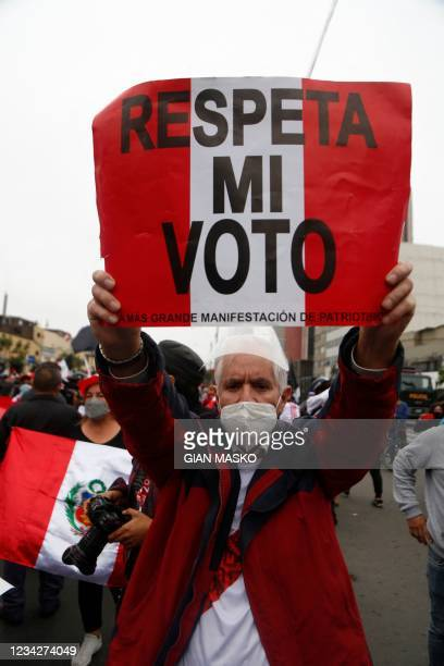 """Detractor of the new Peruvian President Pedro Castillo holds a signal that reads """"Respect my vote"""" during a demonstration in Lima, on July 28, 2021...."""