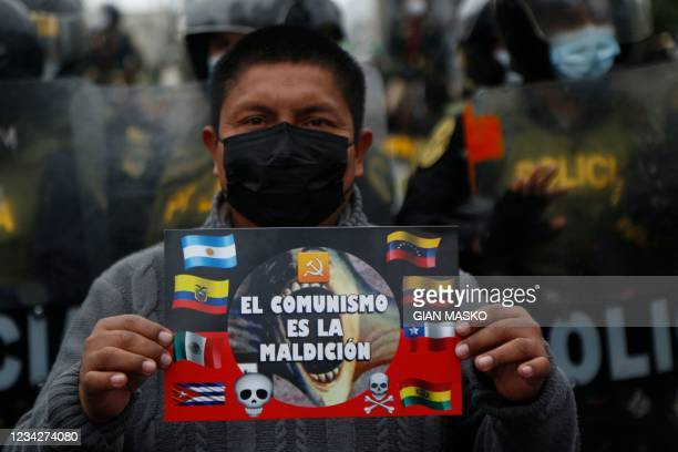 """Detractor of the new Peruvian President Pedro Castillo holds a signal that reads """"Communism is the curse"""" during a demonstration in Lima, on July 28,..."""