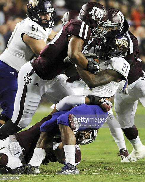 Detrez Newsome of the Western Carolina Catamounts is tackled at the line of scrimmage by Daeshon Hall and Josh Walker of the Texas AM Aggies in the...