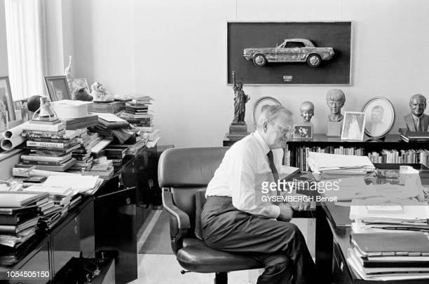 Detroit EtatsUnis février 1987 Lee IACOCCA PDG de la firme automobile Chrysler Ici posant de profil assis à son bureau au milieu de nombreuses piles...