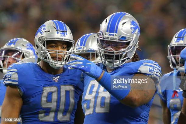 Detroit Lions defensive end Mike Daniels talks with Detroit Lions defensive end Trey Flowers during the second half of an NFL football game against...