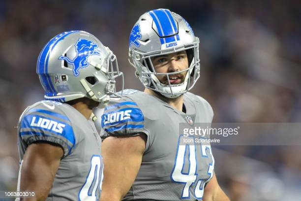 Detroit Lions full back Nick Bellore and Detroit Lions safety Charles Washington walk to the sideline after a play during a regular season game...