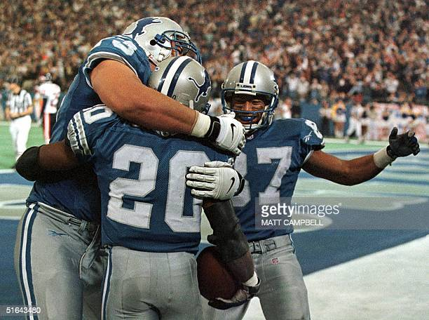 Detroit Lions' Juan Roque and Johnnie Morton congratulate teammate Barry Sanders after he scored a touchdown in the third quarter 27 November at the...