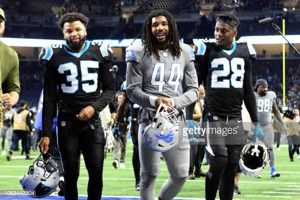 Detroit Lions linebacker Jalen Reeves-Maybin walks off the field with Carolina Panthers cornerback Corn Elder and Carolina Panthers defensive back...