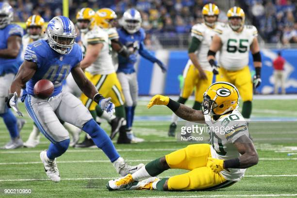 Detroit Lions linebacker Jarrad Davis recovers a fumble during the first half of an NFL football game against the Green Bay Packers in Detroit...
